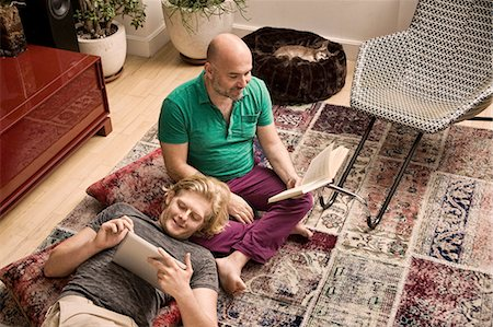 Male couple on living room floor reading book and digital tablet Stock Photo - Premium Royalty-Free, Code: 614-08329498