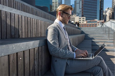 Young businessman sitting on stair typing on laptop, New York, USA Stock Photo - Premium Royalty-Free, Code: 614-08329505