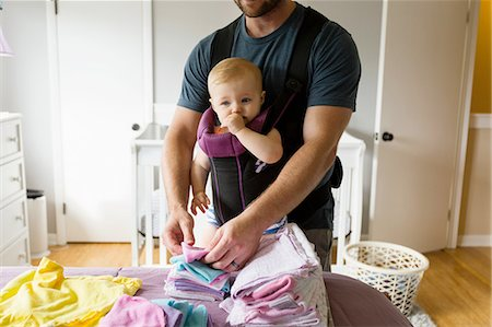 Mid adult man doing chores with baby daughter in baby sling Stock Photo - Premium Royalty-Free, Code: 614-08383545