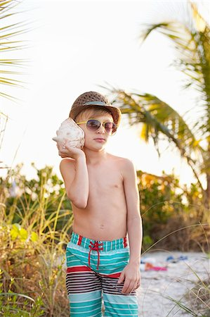 Portrait of boy listening to seashell at beach, Sanibel, Florida, USA Stock Photo - Premium Royalty-Free, Code: 614-08383585