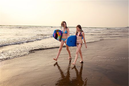 Teenage girl and sister carrying surfboards on beach, Goa, India Stock Photo - Premium Royalty-Free, Code: 614-08383617