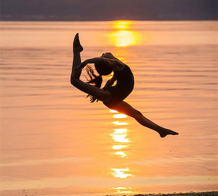 preteen girls stretching - Side view of girl in silhouette by ocean at sunset in mid air, legs apart throwing head back Stock Photo - Premium Royalty-Free, Code: 614-08383634