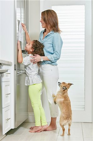 fridge - Side view of mother and daughter in kitchen sticking picture to fridge Stock Photo - Premium Royalty-Free, Code: 614-08383718