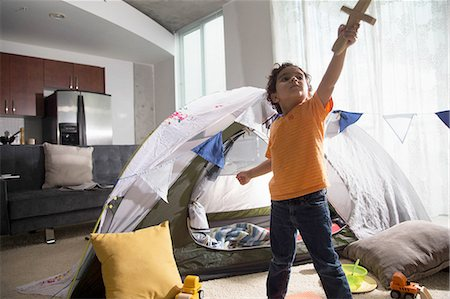 Young boy in living room using tent as den, arm raised, looking up, holding sword Stock Photo - Premium Royalty-Free, Code: 614-08392391