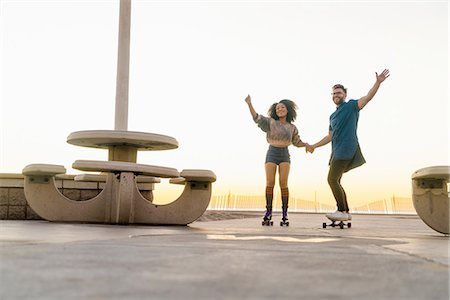 roller skate - Couple using rollerskates and skateboard, holding hands, smiling Stock Photo - Premium Royalty-Free, Code: 614-08392542