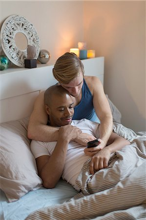 Male couple lying in bed together, looking at smartphone Stock Photo - Premium Royalty-Free, Code: 614-08392612