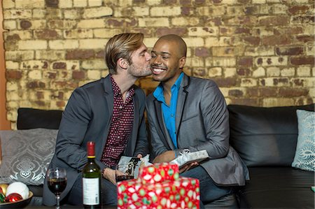 Male couple sitting on sofa, exchanging Christmas gifts, young man kissing partner on cheek Stock Photo - Premium Royalty-Free, Code: 614-08392626
