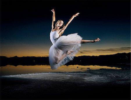 Young female ballet dancer leaping over Bonneville Salt Flats at sunset, Utah, USA Stock Photo - Premium Royalty-Free, Code: 614-08392717
