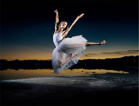 Young female ballet dancer leaping over Bonneville Salt Flats at sunset, Utah, USA Stock Photo - Premium Royalty-Free, Code: 614-08392717
