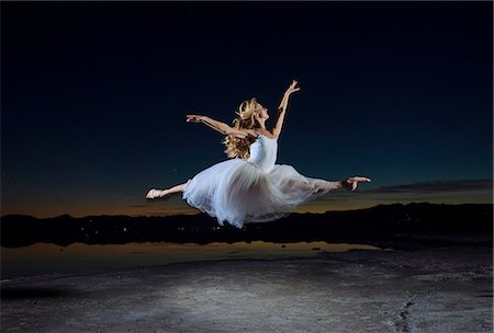 Young female ballet dancer leaping over Bonneville Salt Flats at night, Utah, USA Stock Photo - Premium Royalty-Free, Code: 614-08392718