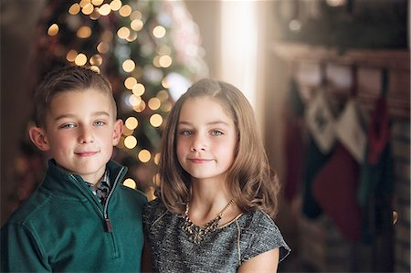 Portrait of girl and boy in front of christmas tree looking at camera smiling Stock Photo - Premium Royalty-Free, Code: 614-08392725
