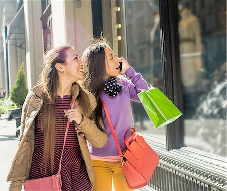 Young female adult twins carrying shopping bags and looking at shop window Stock Photo - Premium Royalty-Free, Code: 614-08392749