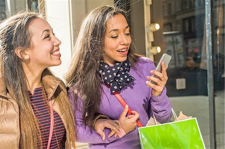 Young female adult twins in city with shopping bags reading smartphone text Stock Photo - Premium Royalty-Free, Code: 614-08392750