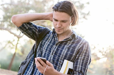 Angled view of young man, hand to head, looking down at smartphone Stock Photo - Premium Royalty-Free, Code: 614-08487867