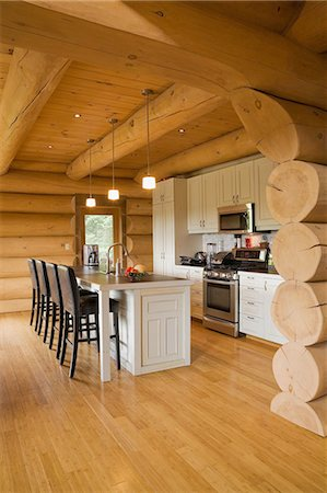 White kitchen cabinets and island and barstools in kitchen of a Scandinavian cottage style log home Stock Photo - Premium Royalty-Free, Code: 614-08488007