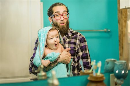 Mirror image of young man and baby son pulling faces in bathroom Stock Photo - Premium Royalty-Free, Code: 614-08535901