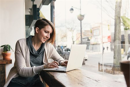 sweater - Female customer sitting in coffee shop window seat typing on laptop Stock Photo - Premium Royalty-Free, Code: 614-08535960
