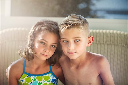 Portrait of boy and girl arms around each other looking at camera smiling Stock Photo - Premium Royalty-Free, Code: 614-08535989