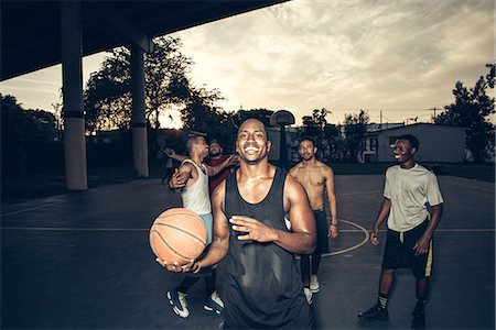 Man with friends on basketball court holding basketball smiling Stock Photo - Premium Royalty-Free, Code: 614-08544690