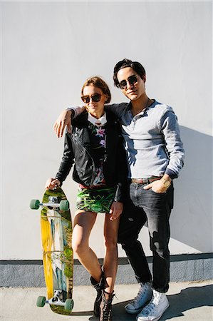 Portrait of young couple outdoors, woman holding skateboard Stock Photo - Premium Royalty-Free, Code: 614-08544714
