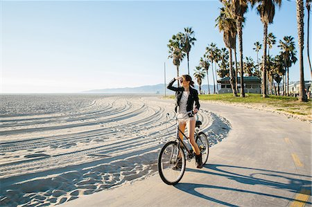 Young woman cycling at beach looking out to sea, Venice Beach, California, USA Stock Photo - Premium Royalty-Free, Code: 614-08544734
