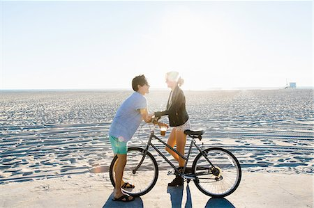 Young couple with bicycle chatting on sunlit beach, Venice Beach, California, USA Stock Photo - Premium Royalty-Free, Code: 614-08544736