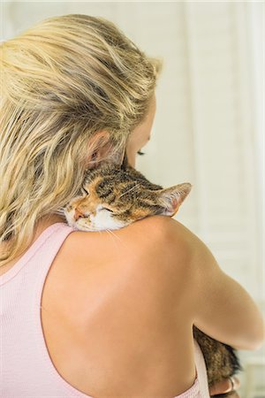 furry - Rear view of woman cuddling cat Stock Photo - Premium Royalty-Free, Code: 614-08544922