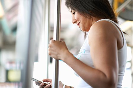 Woman standing on bus reading smartphone texts, Los Angeles, California, USA Stock Photo - Premium Royalty-Free, Code: 614-08544994