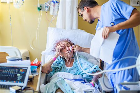 Hospital staff checking on patient on hospital bed Stock Photo - Premium Royalty-Free, Code: 614-08578418