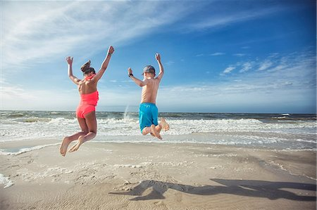 shadow - Rear view of girl and boy on beach arms raised jumping in mid air Stock Photo - Premium Royalty-Free, Code: 614-08578505