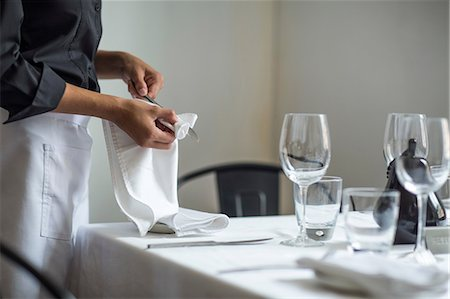 Waitress setting table in restaurant Stock Photo - Premium Royalty-Free, Code: 614-08578563