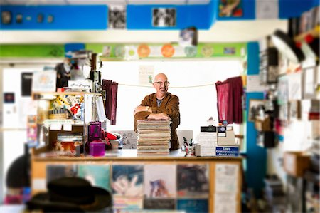 Portrait of mature man in record shop, leaning on stack of records Stock Photo - Premium Royalty-Free, Code: 614-08641284
