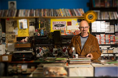 Portrait of mature man in record shop, pricing up records using price gun Stock Photo - Premium Royalty-Free, Code: 614-08641282