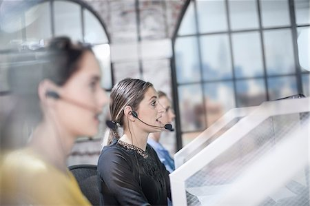 Row of female telephonists working in call centre Stock Photo - Premium Royalty-Free, Code: 614-08641472