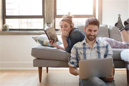 Young couple relaxing at home, young woman reading book, young man using laptop Stock Photo - Premium Royalty-Free, Code: 614-08641561
