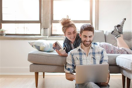 floor - Young couple relaxing at home, looking at laptop Stock Photo - Premium Royalty-Free, Code: 614-08641562