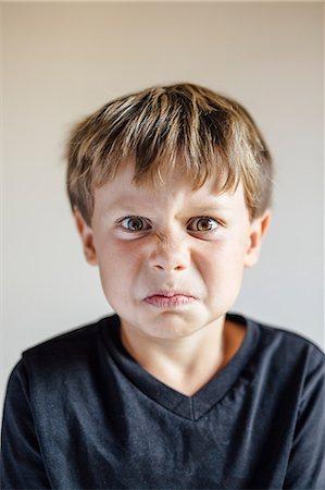 Studio portrait of boy pulling wrinkled face Stock Photo - Premium Royalty-Free, Code: 614-08641686
