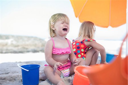 Two sisters sitting on beach, toddler crying, Cape Town, South Africa Stock Photo - Premium Royalty-Free, Code: 614-08641755