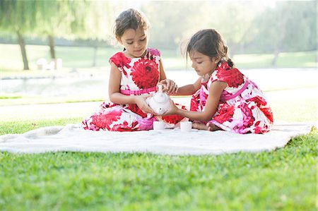 Two young girls playing with tea set on blanket on grass Stock Photo - Premium Royalty-Free, Code: 614-08685072