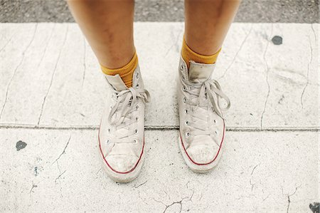 Cropped view of womans feet wearing socks and high tops Stock Photo - Premium Royalty-Free, Code: 614-08685130