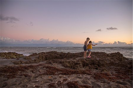 Girl and brother stepping over beach rocks at sunrise, Blowing Rocks Preserve, Jupiter Island, Florida, USA Stock Photo - Premium Royalty-Free, Code: 614-08685195