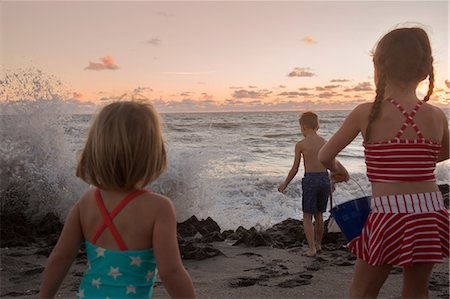 Boy and sisters watching splashing waves at sunrise, Blowing Rocks Preserve, Jupiter Island, Florida, USA Stock Photo - Premium Royalty-Free, Code: 614-08685197