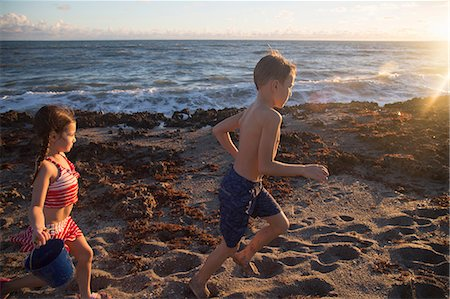 Boy and sister running on beach, Blowing Rocks Preserve, Jupiter Island, Florida, USA Stock Photo - Premium Royalty-Free, Code: 614-08685204