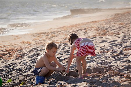 Boy and sister playing with sand on beach, Blowing Rocks Preserve, Jupiter Island, Florida, USA Stock Photo - Premium Royalty-Free, Code: 614-08685222