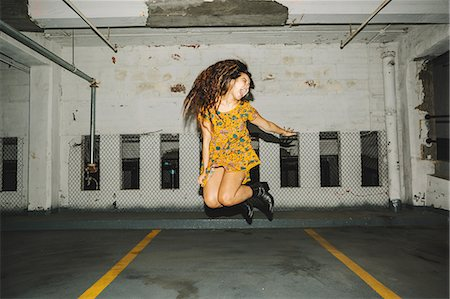 Young woman jumping mid air in indoor parking lot Stock Photo - Premium Royalty-Free, Code: 614-08726728