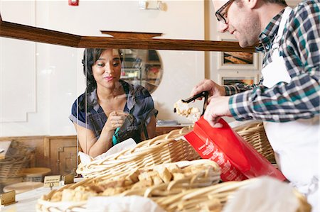 Customer in bakery pointing to baked goods, worker placing goods in bag Stock Photo - Premium Royalty-Free, Code: 614-08720534