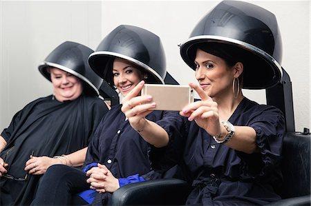 Customers taking selfie under hair dryers Stock Photo - Premium Royalty-Free, Code: 614-08720709