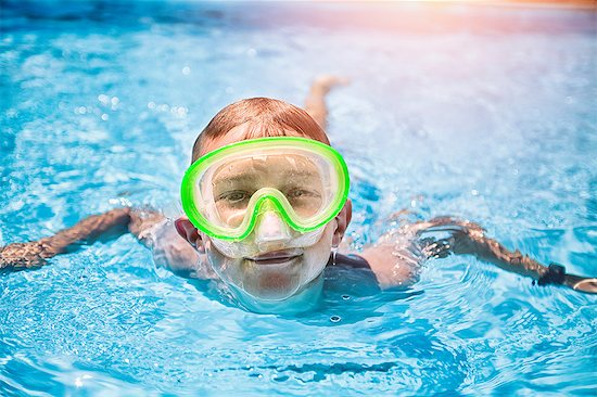 Portrait of boy wearing green scuba mask swimming in sunlit swimming pool Stock Photo - Premium Royalty-Free, Image code: 614-08720973
