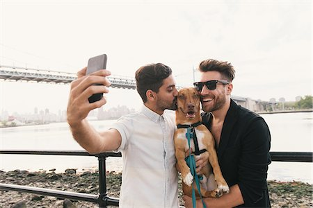 Young male couple on riverside taking smartphone selfie with dog, Astoria, New York, USA Stock Photo - Premium Royalty-Free, Code: 614-08768530