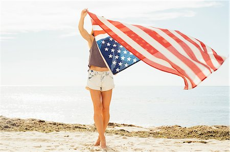 represented - Woman on beach arms raised holding american flag Stock Photo - Premium Royalty-Free, Code: 614-08827386